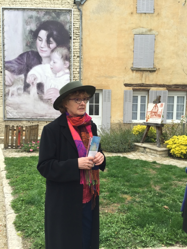Janet Hulstrand conducting a walking tour of Essoyes, a Renoir replica in background